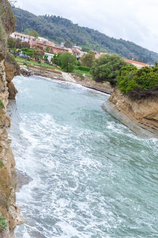 Río que fluye al lado de la colina Agua que acomete abajo de la corriente Casas construidas cerca del cauce del río Vista escénic foto de archivo libre de regalías