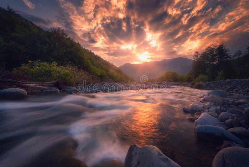 Río rápido de la montaña que fluye en tiempo de la puesta del sol fotos de archivo