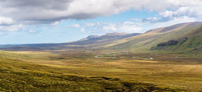 Río serpenteante que atraviesa un valle montañoso imagenes de archivo