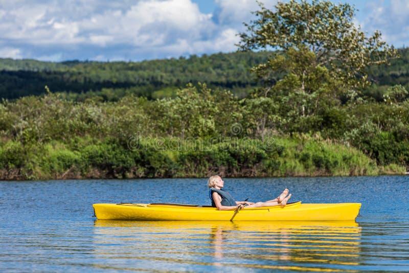 Río tranquilo y mujer que se relajan en un kajak imagenes de archivo