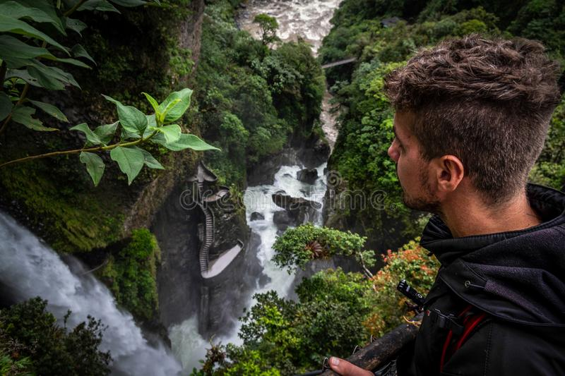 A tourist who contemplates the incredible and powerful waterfall surrounded by a tropical forest. stock images