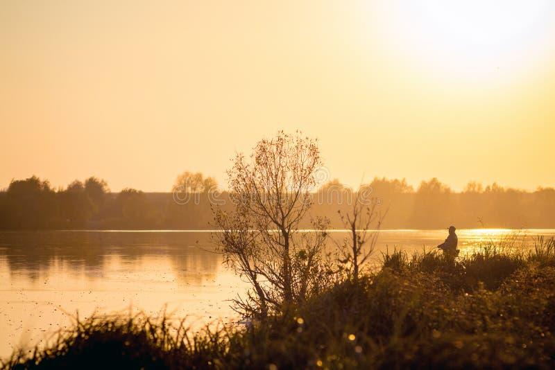 Río y pescador en la orilla durante el sunset_ fotografía de archivo libre de regalías