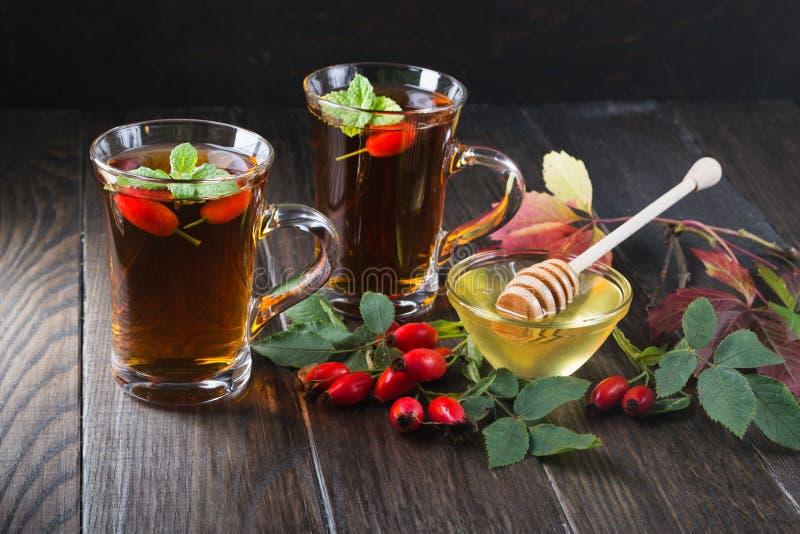 Różana modna herbata w przejrzystej filiżance z miodowymi i świeżymi jagodami Witaminy C napój zdjęcia stock