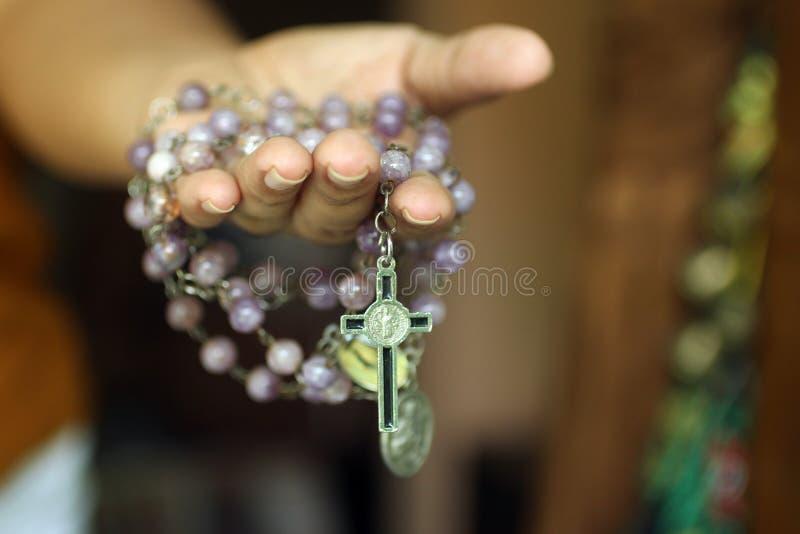 Różaniec w jeden ręce Młody młodzieżowy damy mienia różaniec z otwartą ręką Żeńskie ręki trzyma różana z jezus chrystus krzyżem l obrazy royalty free