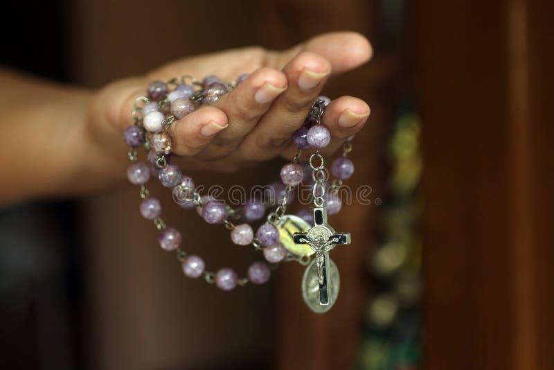 Różaniec w jeden ręce Młody młodzieżowy damy mienia różaniec z otwartą ręką Żeńskie ręki trzyma różana z jezus chrystus krzyżem l obraz royalty free