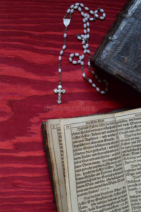 Różaniec z starą antyczną książką na czerwonym drewnie obraz stock