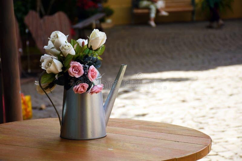 Różany bukiet w starej metalu podlewania puszce na drewnianym stole przy ulicznym cukiernianym tłem zdjęcie royalty free