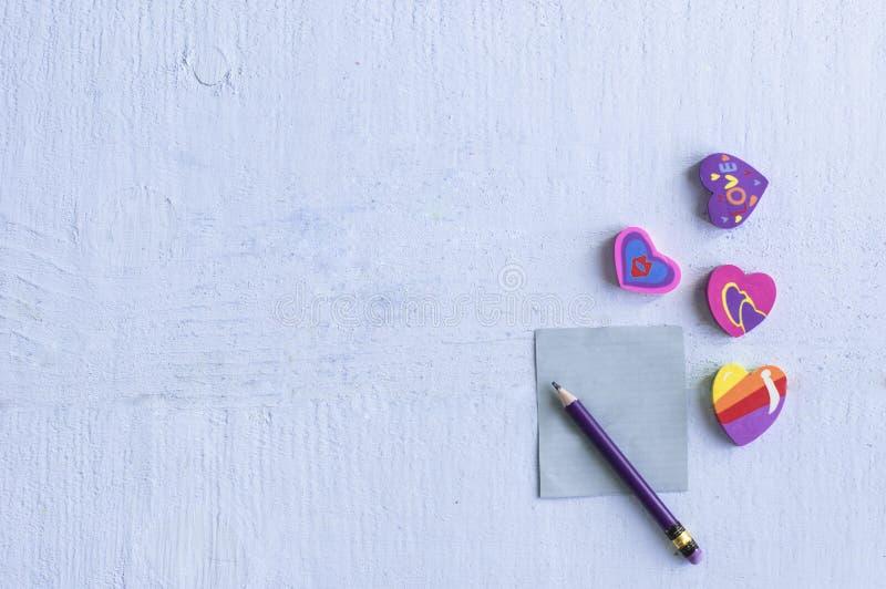Różna gumka w formie serca z ołówkiem z pustym małym nutowym papierem i obrazy royalty free