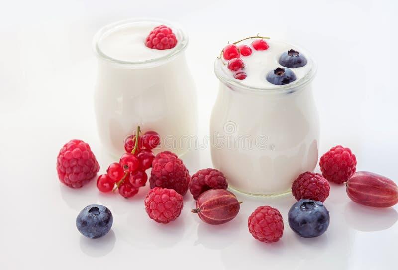 Różne dojrzałe jagody i domowej roboty jogurt na światła białego tle Dobra śniadaniowa miękka selekcyjna ostrość fotografia stock