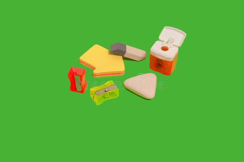 Różne gumki i ostrzarki na zielenieją powierzchnię fotografia stock