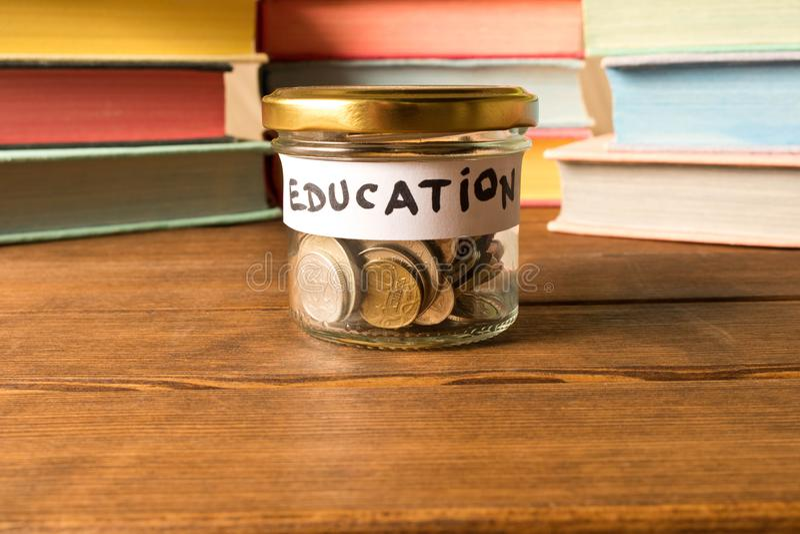 Różne monety w szklanym słoju na tle książki bucharest biuro c e zdjęcia royalty free