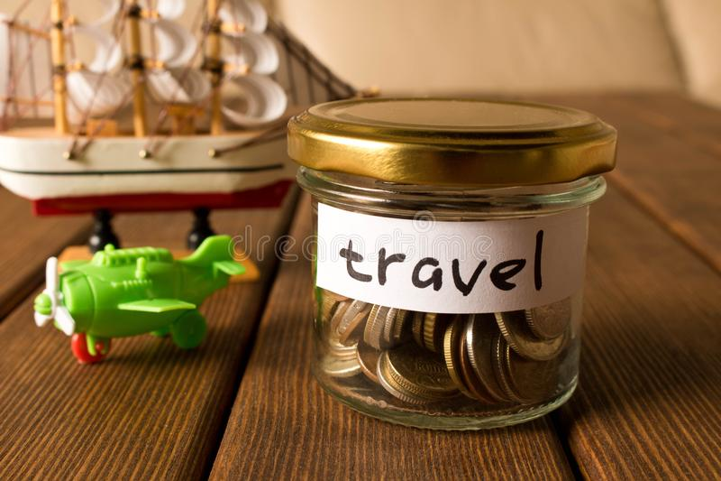 Różne monety w szklanym słoju Pojęcie podróży savings fotografia royalty free