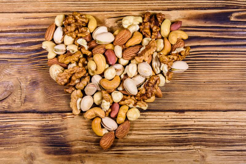 Różne orzechy migdały, nerkowiec, orzech laskowy, pistacje, orzechy włoskie w kształcie serca na drewnianym stole Mączka wegetari obraz royalty free