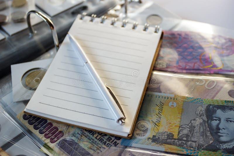 Różne stare poborca monety, banknoty z piórem i notatnikiem i, zamazany tło zdjęcia stock
