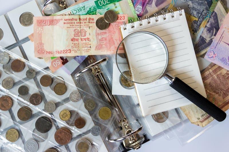 Różne stare poborca monety, banknoty z powiększać i - szkło i notatnik, zamazany tło zdjęcie stock
