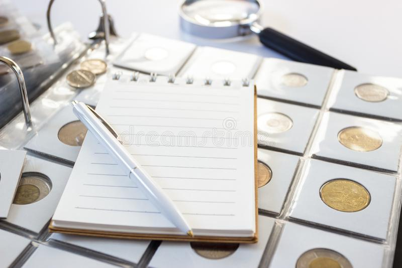 Różne stare poborca monety, notatnik i pióro i, zamazany tło obrazy royalty free