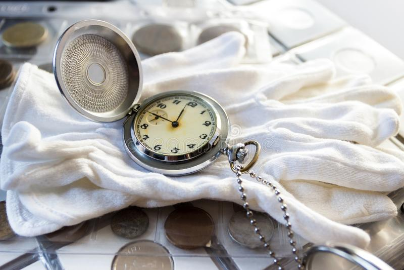 Różne stare poborca monety z kieszeniowym zegarkiem, zamazany tło zdjęcie royalty free