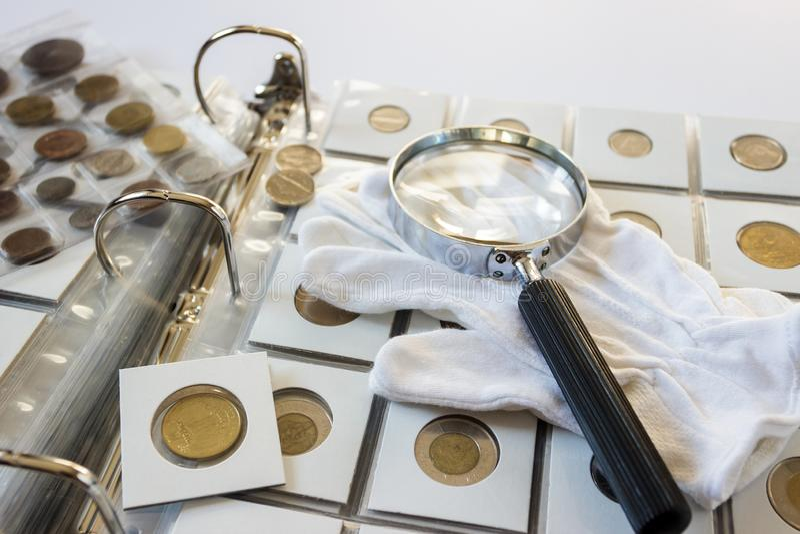 Różne stare poborca monety z powiększać - szkło, zamazany tło obraz stock