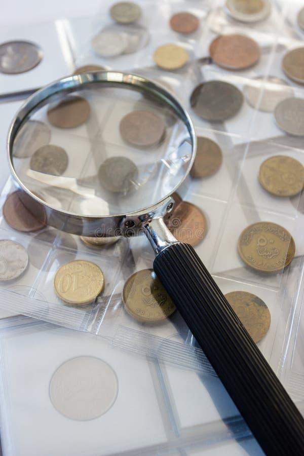 Różne stare poborca monety z powiększać - szkło, zamazany tło obrazy stock