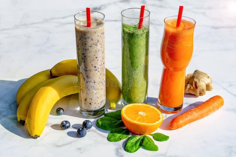 3 różnego rodzaju smoothies ze składnikami na marmurowym stoliku, gigner banan blueberry szpinak marchew obrazy royalty free