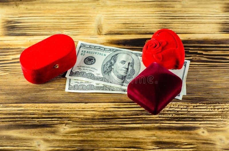 Różni czerwoni biżuterii pudełka i dolarowi banknoty na drewnianym stole fotografia stock