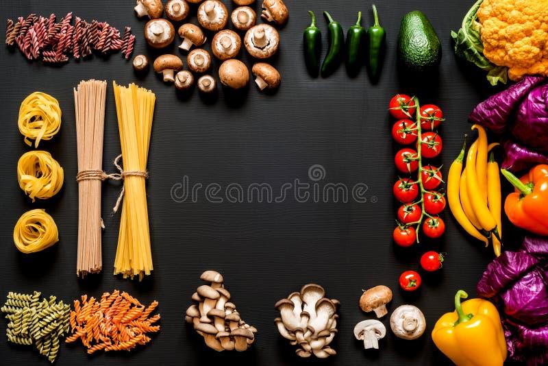 Różni kolorowi Świezi surowi składniki dla zdrowego jarskiego kucharstwa na czarnym tle z bezpłatnej kopii przestrzenią mieszkani zdjęcie stock