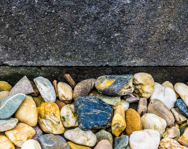 Różni kolory otoczaków kamienie przeciw błękitnej granit ścianie uprawiają ogródek dekoraci tła teksturę obraz stock