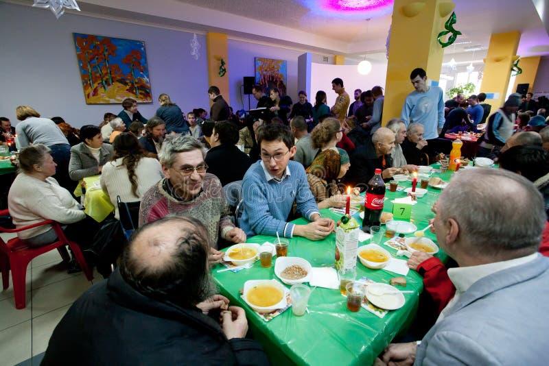 Różni ludzie opowiada przy stołami przy Bożenarodzeniowym dobroczynność gościem restauracji dla bezdomny obraz stock