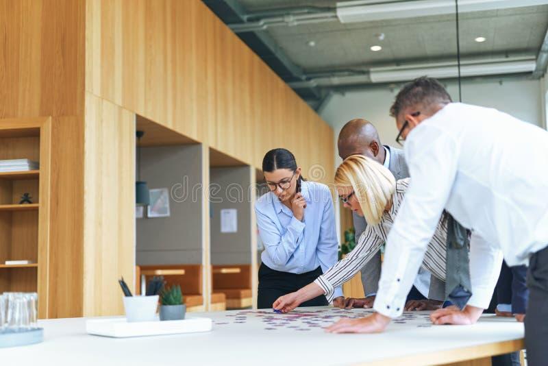 Różni przedsiębiorcy próbujący rozwiązać zagadkę w biurze zdjęcia stock