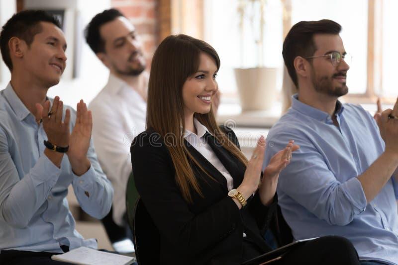 Różni przedsiębiorcy siedzą z oklaskami podczas seminarium fotografia stock