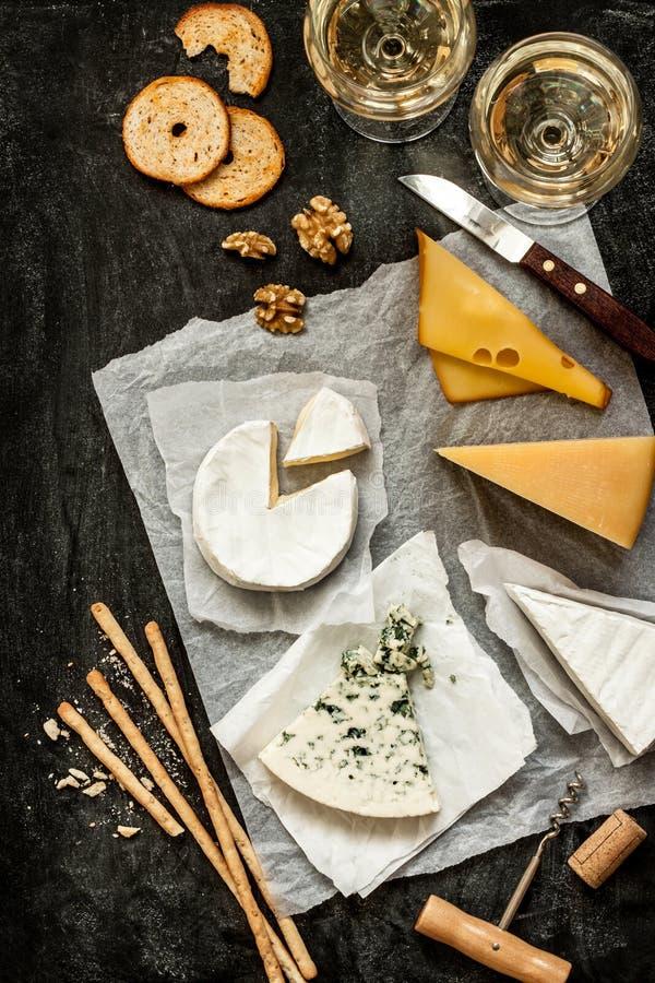 Różni rodzaje sery, biały wino i przekąski na czerni, fotografia stock