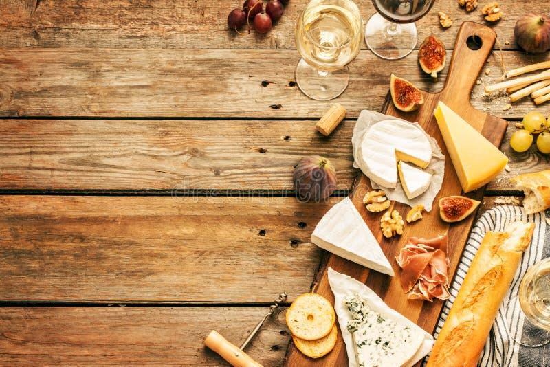 Różni rodzaje sery, wino, baguettes, owoc i przekąski, zdjęcie stock