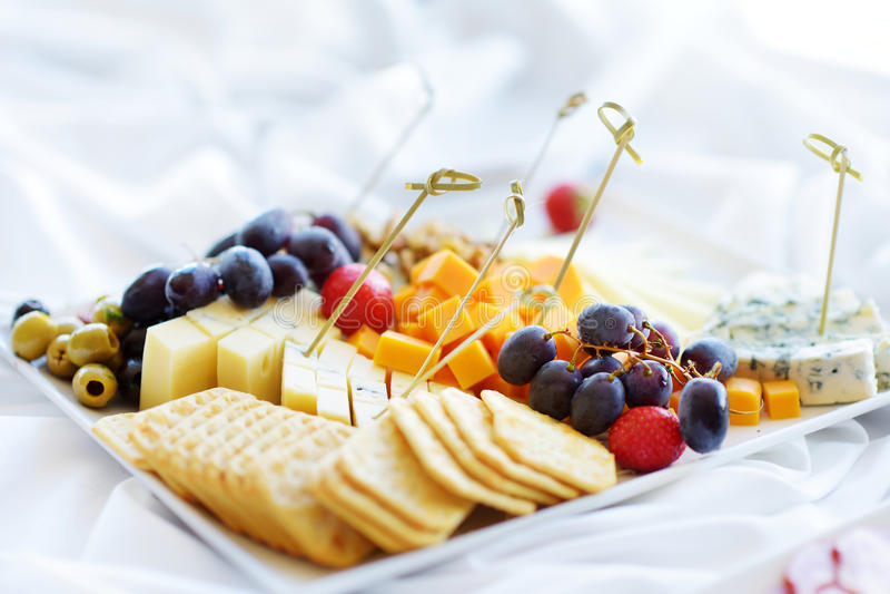 Różni rodzaje wino przekąski: sery, krakers, owoc i oliwki na bielu stole, zdjęcia stock
