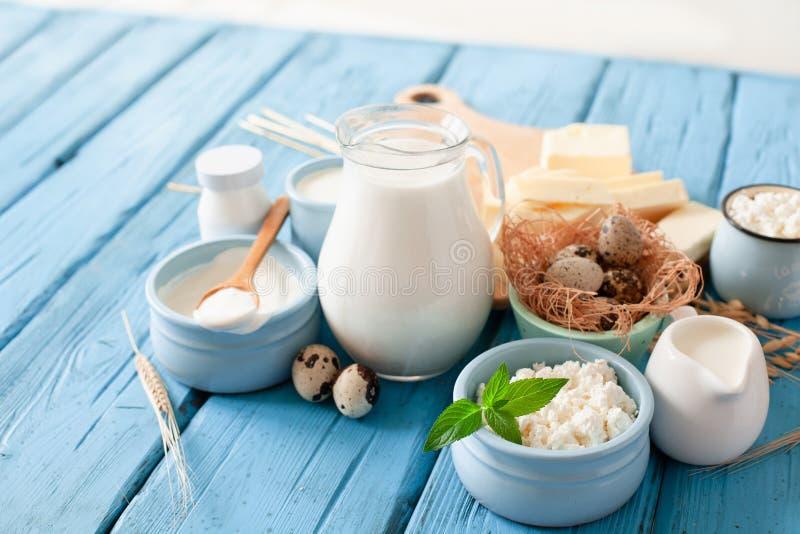Różni typy nabiały na błękitnym drewnianym tle: mleko, kwaśna śmietanka, chałupa ser, ser, śmietanka, jogurt, jajko, masło fotografia royalty free
