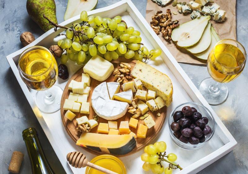 Różni typy ser na drewnianej deski, oliwki, owoc, migdału i wina szkłach na białej tacy, zdjęcie stock