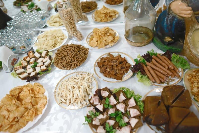 Różnic przekąsek różni niezdrowi krakersy, solone dokrętki, słoma piwo i przekąski, frytki, arachidy, bekon, ogórki, fotografia stock