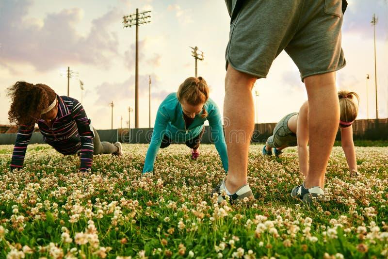 Różnorodna grupa kobiety podczas sprawności fizycznej szkolenia robi Ups przy zmierzchem w natura parku fotografia stock