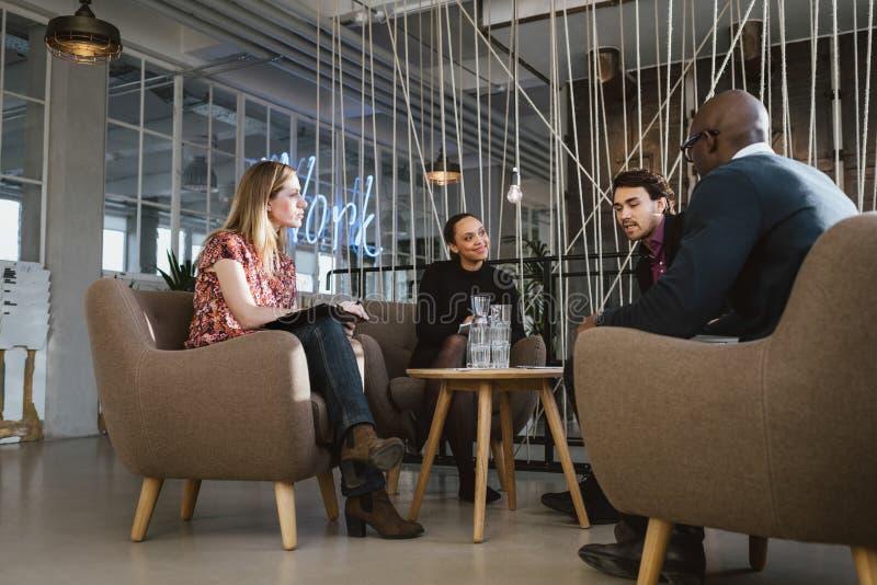 Różnorodna grupa młodzi ludzie ma spotkania w lobby obrazy royalty free