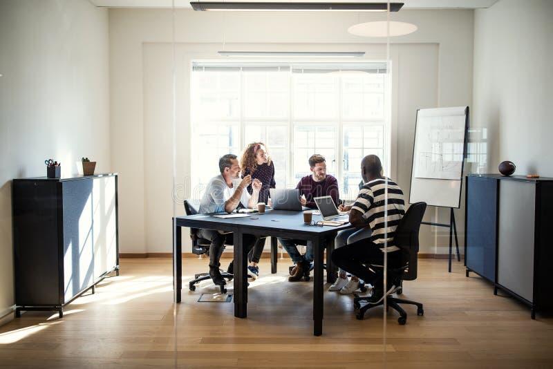Różnorodna grupa projektanci spotyka wpólnie wokoło biurowej zakładki obrazy stock