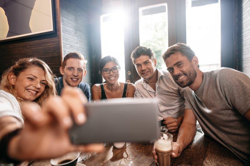 Różnorodna grupa przyjaciele bierze selfie przy kawiarnią obraz royalty free