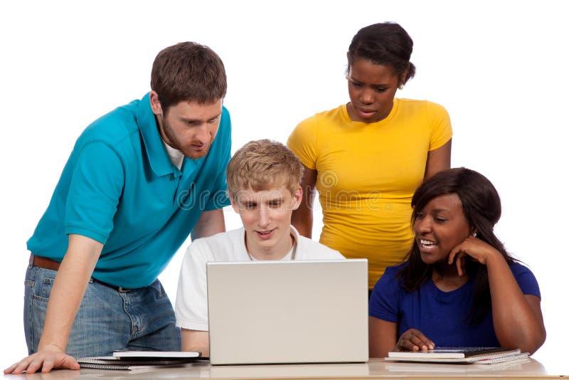 Różnorodna grupa studenci collegu, przyjaciele patrzeje komputer/ obraz stock