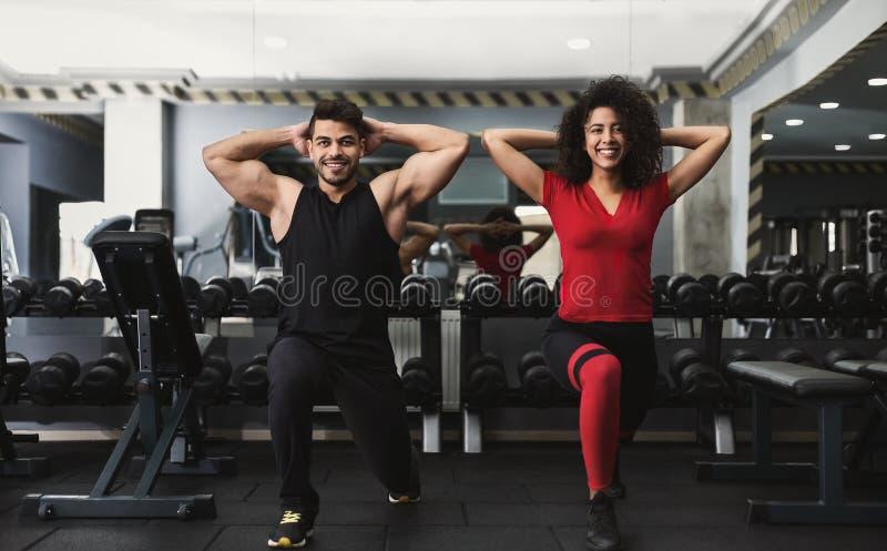Różnorodna sporty para opracowywa w gym wpólnie obraz royalty free