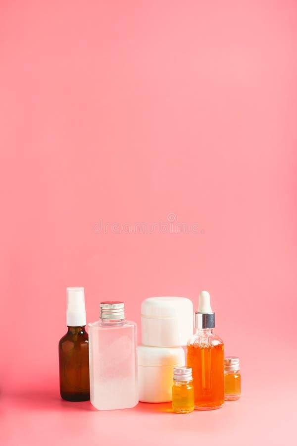 Różnorodne butelki, słoje i zbiorniki z kosmetykami na menchiach, zdjęcie stock