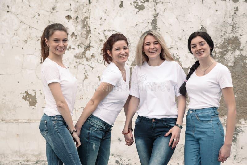 Różnorodne dziewczęta w koszulkach i dżinsach nad ścianą uliczną obraz royalty free