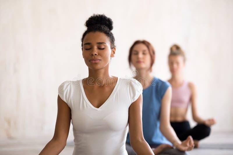 Różnorodne dziewczyny siedzi w lotosowej pozycji robi joga fotografia stock