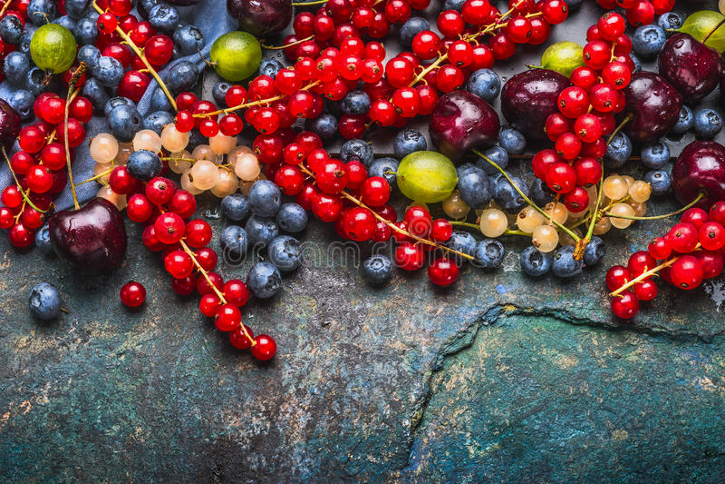 Różnorodne lato jagody: agrestów, czerwieni i białych rodzynki, wiśnie, czarne jagody na ciemnym nieociosanym tle, odgórny widok zdjęcia royalty free