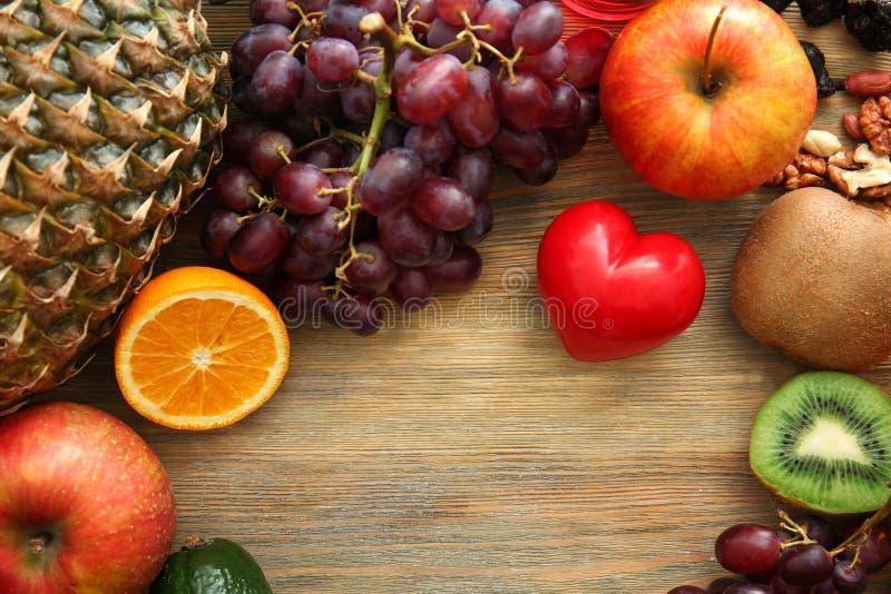 Różnorodne owoc z czerwonym sercem na drewnianym tle poj?cia zdrowe jedzenie fotografia stock