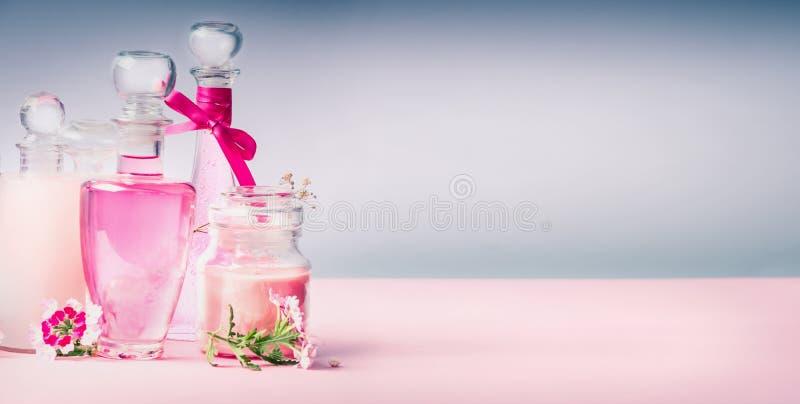 Różnorodnego Kosmetycznego produktu szklane butelki na menchiach zgłaszają biurko przy szarym tłem, frontowy widok, sztandar zdjęcia stock