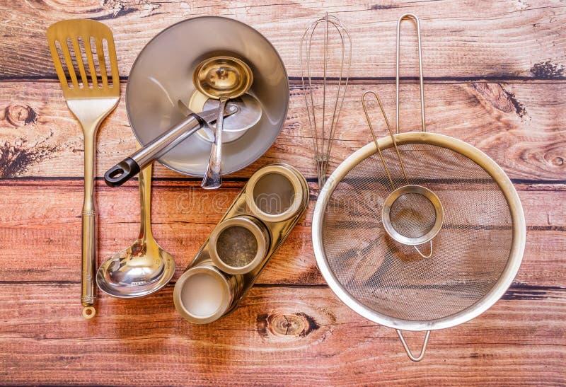 Różnorodnego metalu kuchenni naczynia na drewnianym tle, odgórny widok fotografia stock