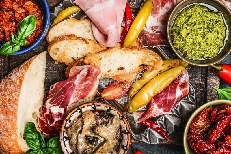 Różnorodni antipasti, ciabatta chleb, pesto i baleron, odgórny widok obraz royalty free